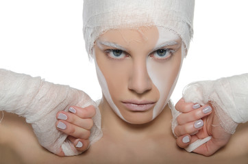 Portrait of woman with white face art and bandage
