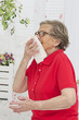 Senior woman sneezing into a tissue