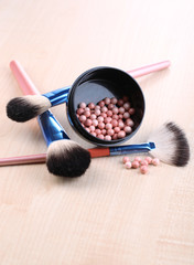 Powder balls and brushes on wooden background