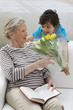 Grandson offering Grandmother a flower