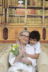 Little boy giving flowers to his grand mother in the library