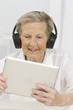 senior woman enjoying music and watching videos on tablet pc