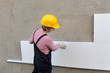 Female worker placing styrofoam sheet insulation to wall