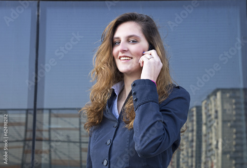 young business woman talking on the phone outdoors