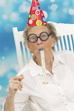 happy mature woman with funny big eye-glasses , and noise maker