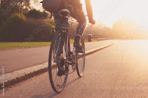 Młodej kobiety kolarstwo w parku przy zmierzchem