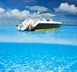 Beach and motor boat with white sand bottom underwater view