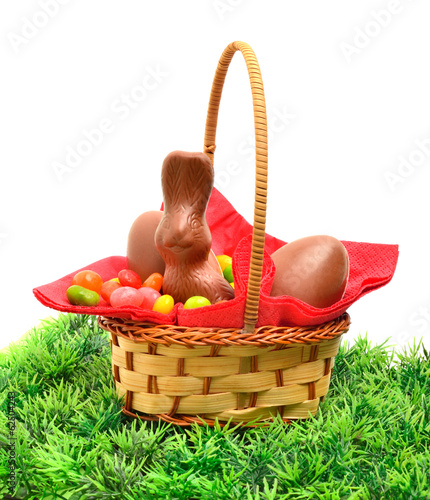 Easter chocolate bunny and eggs in the basket on the grass