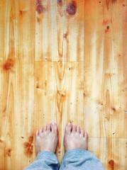 Женские стопы на деревянном полу