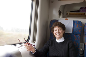 happy female retired middle age senior on first class train in P