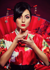 woman in red Asian costume arranging Japanese tea ceremony