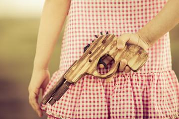 Girl holding wooden gun