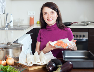 Smiling girl cooking fish pie with  salmon