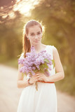 beautiful girl with bouquet of lilac