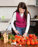 brunette long-haired housewife cooking with  tomatoes