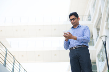 indian business man texting or surfing on a phone