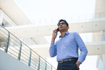 young indian business male in formal with a phone