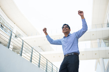 indian business male celebrating success with office background