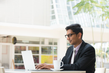 young indian business man on laptop and coffee