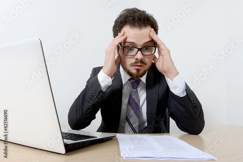 Worried young businessman with laptop and documents