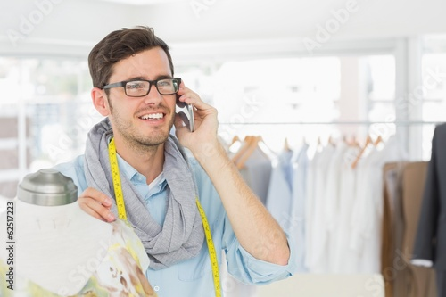 Fashion designer working on dress while using mobile phone