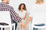 Therapist smiling at reconciled couple holding hands