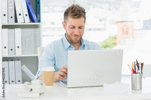 Smiling man working at his desk on laptop