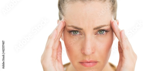Woman with headache touching her temples frowning at camera