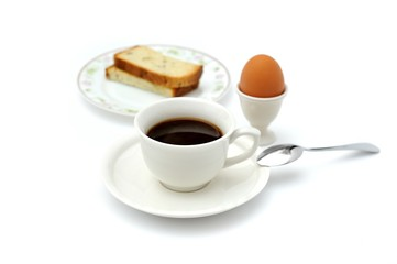 A cup of black coffee, breakfast bread and egg cup
