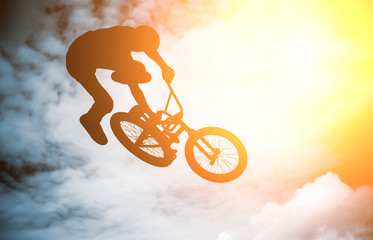 Silhouette of a man with bike.