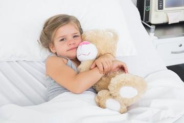 Cute girl embracing teddy bear in hospital bed