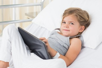 Sick girl with digital tablet in hospital bed
