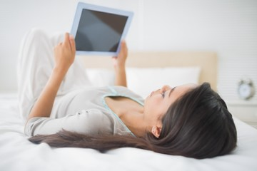 Pretty young girl lying on bed looking at her tablet pc