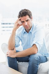 Man with headache sitting on the couch looking at camera