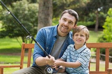 Father and son fishing on park bench