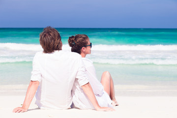 back view of young couple lying on beach