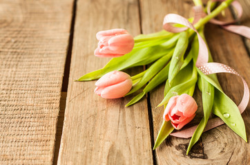 Spring bouquet of pink tulips on vintage wood table
