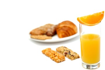 Breakfast bread, oat meal bars and a glass of orange juice