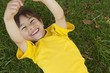 Young boy lying on grass at park