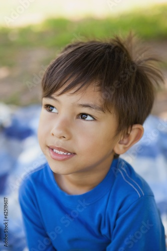 Boy looking away in thought at park