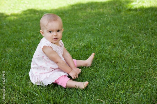 Cute baby sitting on grass at park
