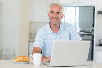 Happy man using his laptop at breakfast
