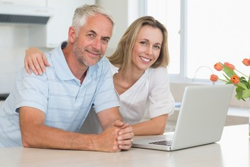 Cheerful couple using laptop together smiling at camera
