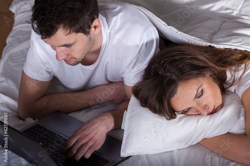 Sleeping wife and husband using computer