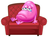 A crying monster sitting on a red sofa