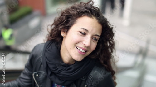 Happy young woman going up on a moving escalator