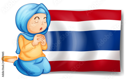 A muslim praying in front of the Thailand flag