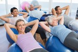 Smiling people stretching on exercise balls in gym