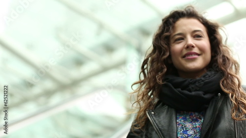 Happy young woman on a moving escalator