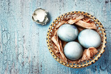 Blue easter eggs in a wattled plate on a textured background. Ru